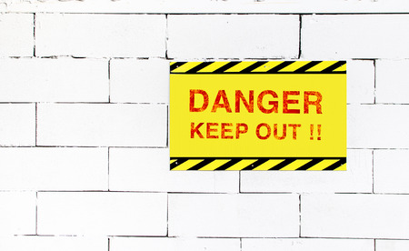 danger signs: Cement block wall with Danger keep out sign