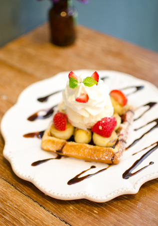 waffle with ice cream topping with strawberry and banana on wooden table  photo