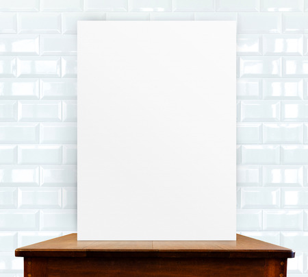 blank photo frame on wood table at white ceramic tiles wall photo