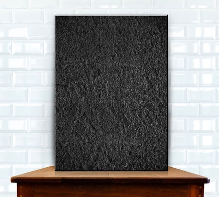 blank stone on wood table at white ceramic tiles wall photo