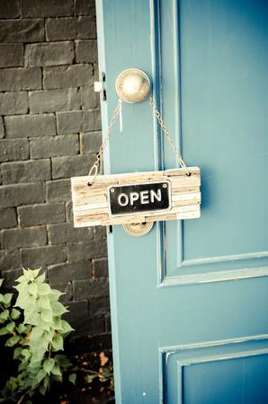 door leaf: open label hanging on blue door in garden. Stock Photo