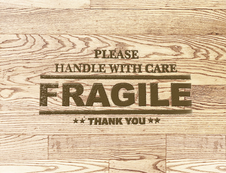 fragile word stamp on wood plank background. photo
