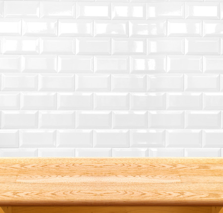 bathroom tile: Empty wood table and ceramic tile brick wall in background. product display template.