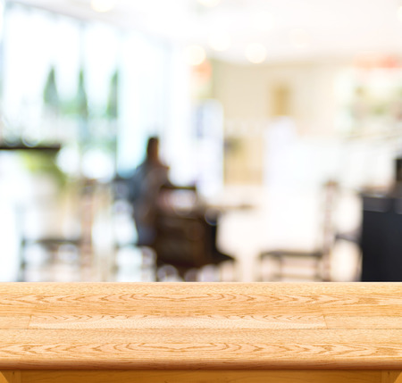 shop interior: Empty wood table and blurred cafe light background.