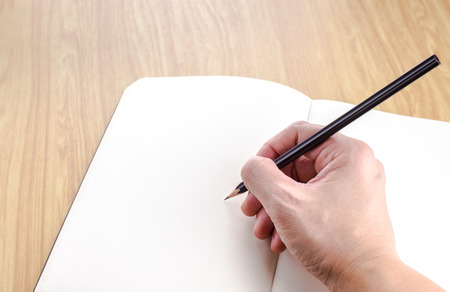 open plan: Hand holding black pencil writting on blank open notebook on wood table,business template.