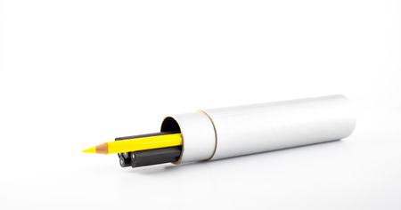 pencil box: Yellow pencil outstanding from black pencil in round pencil box on white background.