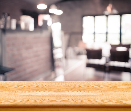 blur: Empty wood table top with coffee shop blur with bokeh background,Product display template.