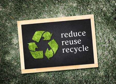 """reduce reutiliza recicla: Vista superior de s�mbolo de reciclaje y  palabra """"reduce la reutilizaci�n recicla """" en la pizarra con desaturated fondo de la hierba verde, el concepto de Eco."""