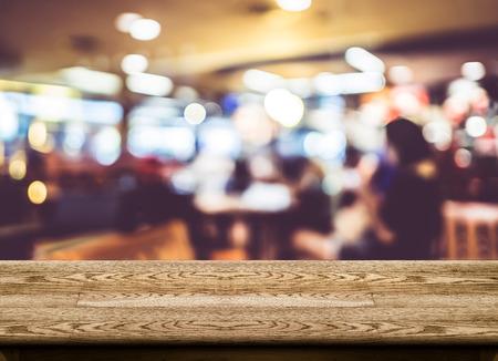 커피 숍 빈 나무 테이블 상단은 나뭇잎 배경, 제품 디스플레이 템플릿을 흐리게.