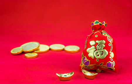 Chinese new year decoration: red felt fabric packet or ang pow with word prosperous and golden ingots on red fabric. photo
