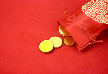 ang: Chinese new year decoration: red fabric packet or ang pow with chinese style pattern and golden coin on red felt fabric