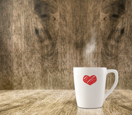 Hot White coffee cup with red heart on wood floor and blur wood room,Leave space for adding content photo