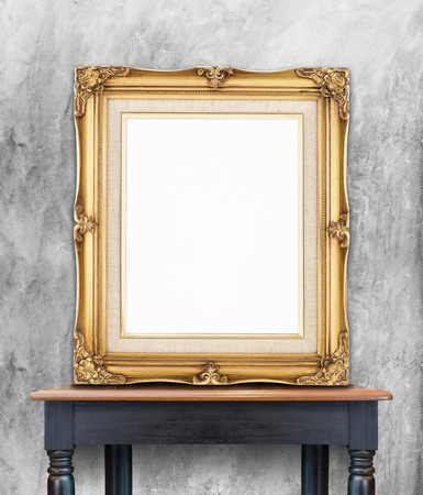 Blank vintage golden photo frame lean at gray color concrete wall on wood table,Template Mockup for add picture.. Фото со стока