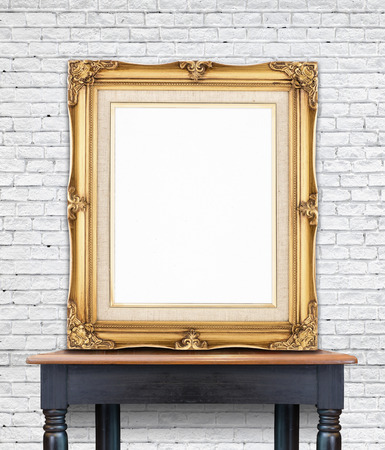 interior layout: Blank vintage golden photo frame lean at white brick wall on wood table,Template Mockup for add picture. Stock Photo