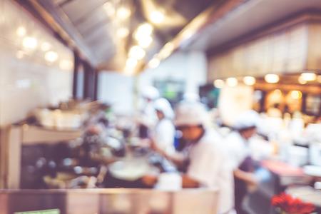背景がぼやけ: オープン キッチンで調理するシェフのグループ、顧客は食品売り場、光のボケ味と料理のシェフに調理彼らを見ることができます
