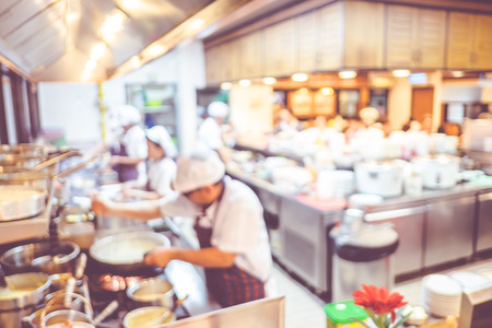 Blurred background : Groups of Chef cooking in the open kitchen,customer can see they cooking at food counter, cooking chef with light bokeh