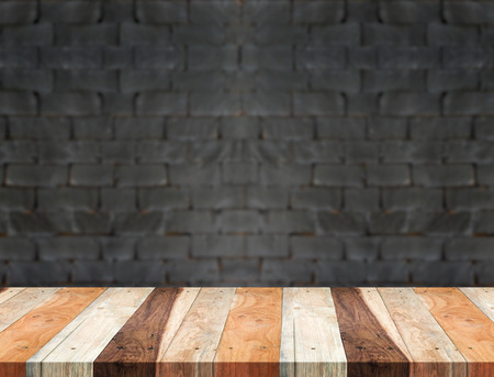 urban background: Empty tropical wood table and blurred black brick wall background. product display template.Business presentation.