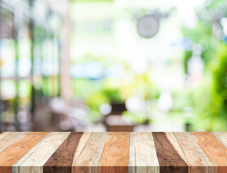 cafe: Empty tropical wood table and blurred garden cafe light background. product display template.Business presentation.
