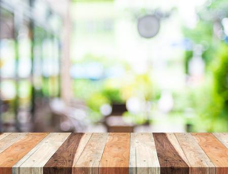 decoracion mesas: Vaciar mesa de madera tropical y el fondo borroso de luz cafeter�a del jard�n. exhibici�n del producto presentaci�n template.Business. Foto de archivo