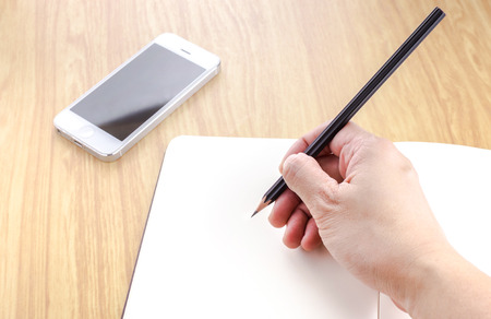 Hand holding black pencil and writing on blank open notebook with smartphone beside it on wooden table,Digital media concept photo