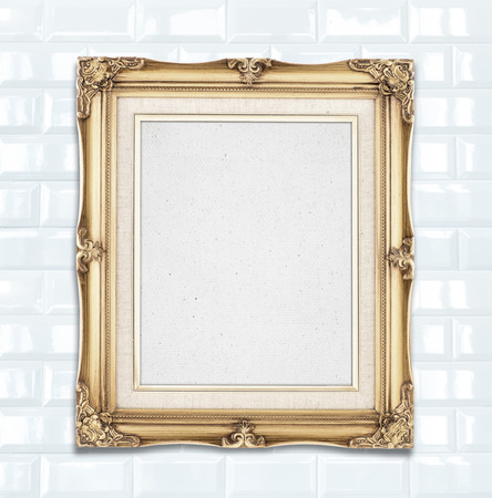 presentaion: Blank Gold color vintage photo frame hanging on white ceramic tile wall,template for adding your photo.