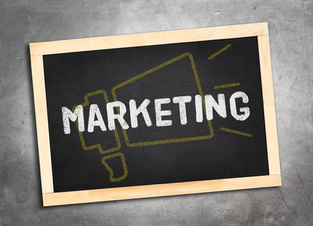 lay: marketing word and yellow megaphone icon on blackboard lay on grunge cement floor ,Business concept..