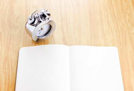 Blank open notebook with silver alarm clock beside it on wooden table,Template mock up for adding your content. photo