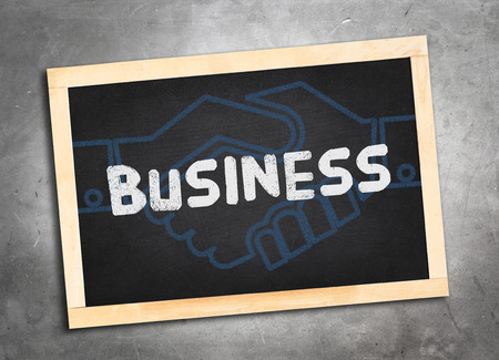 lay: Business word and blue handshake icon on blackboard lay on grunge cement floor ,Business concept Stock Photo