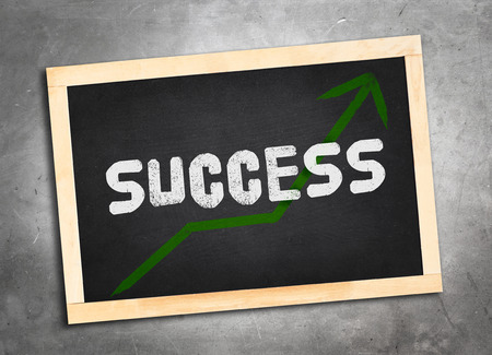 lay: success word and green upper arrow on blackboard lay on grunge cement floor ,Business concept