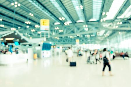 airport arrival: Blurred background : Traveler at airport terminal blur background with bokeh light,Vintage filter.