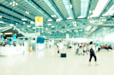 Blurred background : Traveler at airport terminal blur background with bokeh light,Vintage filter.