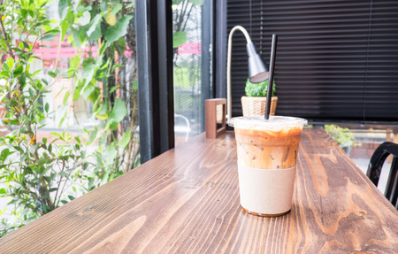 Ice coffee on wood table beside window in coffee shop at garden.