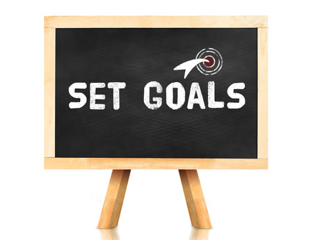set goals: Set goals word and arrow icon on blackboard with easel and reflection on white background,Business concept.