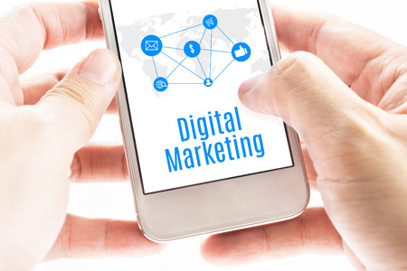 Close up Two hand holding smartphone with Digital Marketing word and icons, Digital Marketing concept. photo