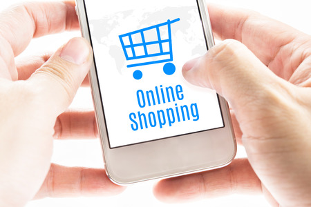 Close up Two hand holding smartphone with Online shopping word and cart icons, Digital Marketing concept. photo