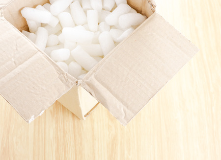 packaging equipment: Open Crumpled brown box with white foam shockproof inside on wood table.