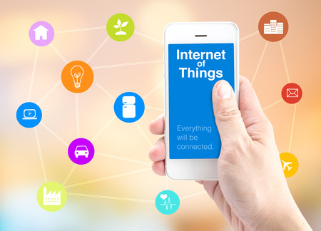 internet: Hand holding smartphone with Internet of things (IoT) word and object icon and blur background, Digital Marketing concept. Stock Photo