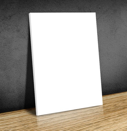 Blank white poster frame at wooden floor and black concrete wall, Canvas frame template mock up for adding your content,Business concept. photo