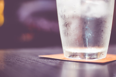 Vintage filter : Cold glass of water on wooden table at restaurant.