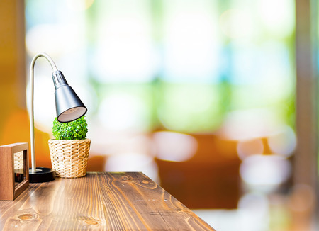 Houten tafel met lamp en foto frame op wazig tuincafé achtergrond, Template mock-up voor de weergave van producten. Stockfoto