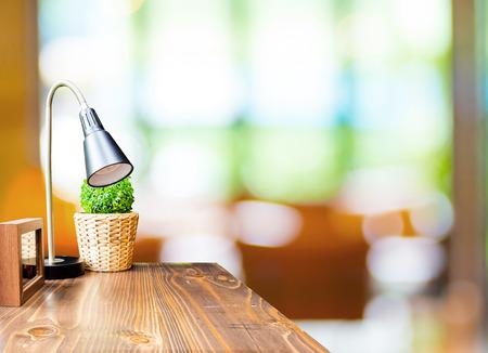 decoracion mesas: Mesa de madera con l�mpara y marco de fotos en el fondo borroso cafeter�a jard�n, Plantilla maqueta para la exhibici�n de productos.
