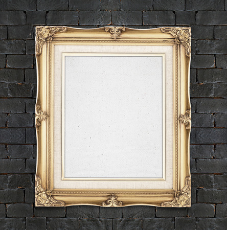 presentaion: Blank Gold color vintage photo frame hanging on black brick wall,template for adding your photo.