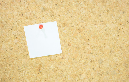 red pushpin: notepad with red pushpin on corkboard.