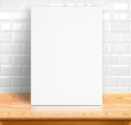 Black White paper poster lean at white ceramic tiles wall and wood table,Template mock up for adding your text. Stock Photo