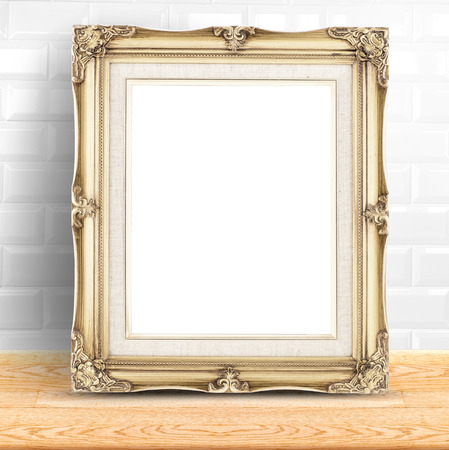Golden Vintage photo frame at white ceramic tiles wall and wooden table,Template mock up for display of product. photo
