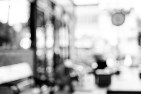 Blurred Woman reading newspaper in garden of Coffee shop with bokeh.