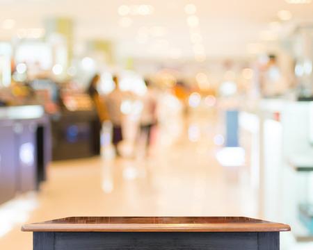 plaza comercial: Vaciar Tablero de madera con centro desenfoque de fondo tienda Foto de archivo