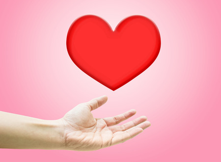 woman floating: Heart shape are floating on open woman hand on pink background.