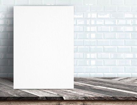 Black White paper poster lean at white ceramic tile wall and tropical wood table,Template mock up for adding your text. photo