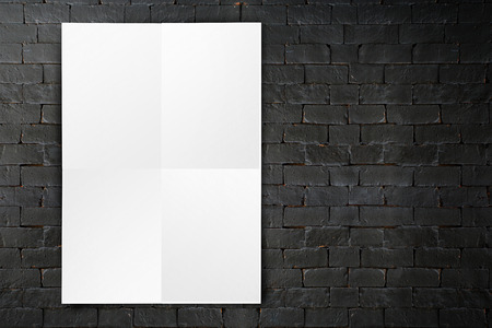 tile wall: Blank folded paper poster hanging on black brick wall,Template mock up for adding your design.